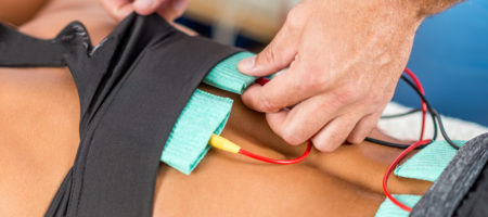 Electrical stimulation in physical therapy. Therapist positioning electrodes onto a female athlete's lower back muscles